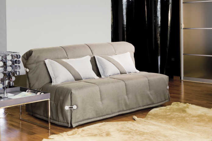 Ginger fold out sofa bed with headboard completed with lumbar cushion with decorative diagonal stipes.