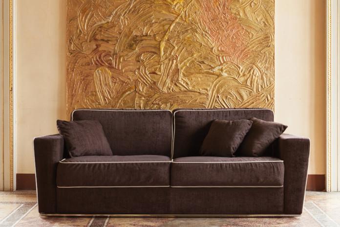 Retrohs Sofa lässt sich in ein Bett verwandeln. Die Kontrastbordüre heben die Form der Armlehnen, die im Unterteil dünner werden.
