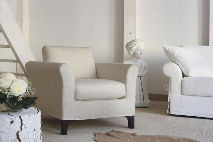 Greta est un fauteuil de salon en tissu blanc et pieds en bois